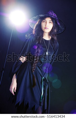 Feeling Witchy.  Attractive mixed race teen wearing a witch costume.  Background light and lens flare included in image.