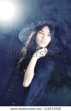Feeling Witchy.  Attractive mixed race teen wearing a witch's costume.  Background light, fog and lens flare included in image.