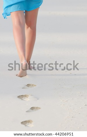 Feet and legs of woman walking on beach in warm early evening light.