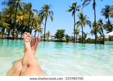 Feet at holiday resort with palm trees - stock photo
