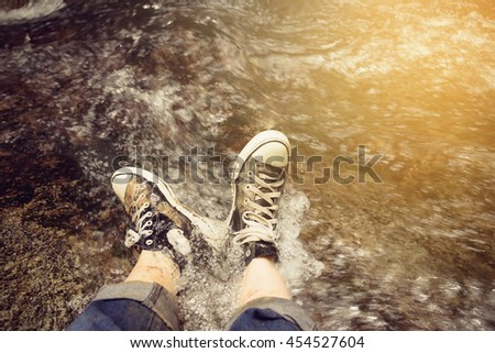 Feet Couple Man hiking outdoor Lifestyle Travel concept  waterfall in the forest Vintage Tone - stock photo