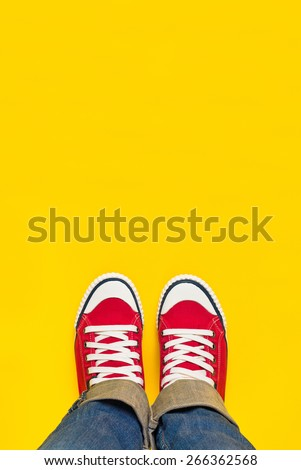 Feet From Above Concept, Teenage Person in Red Sneakers Standing on Yellow Background, B;lank Copy Space in Front. - stock photo