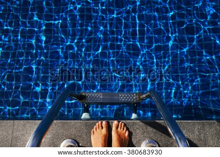 Feet from the top front of the pool with blue water - stock photo