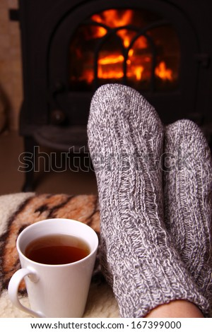 Feet in front of a fireplace - stock photo