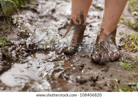 Feet in mud close-up - stock photo