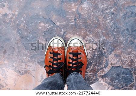Feet in sneaker on concrete floor. - stock photo