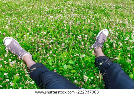 Feet in sneakers on green grass