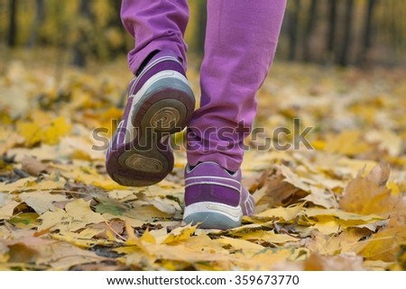 Feet in sneakers. to go on leaves. walking active lifestyle .fioletovy. foot. feet in footwear. autumn obuv.udobny cross-countries for walks.