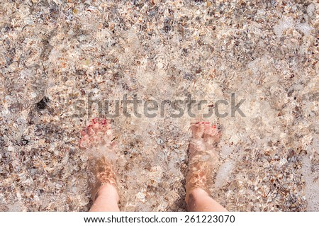 Feet in the sea on a sandy beach. Travel background. Small depth of field - stock photo