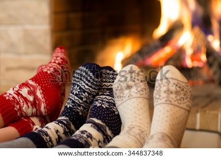 Feet in wool socks near fireplace in winter time - stock photo