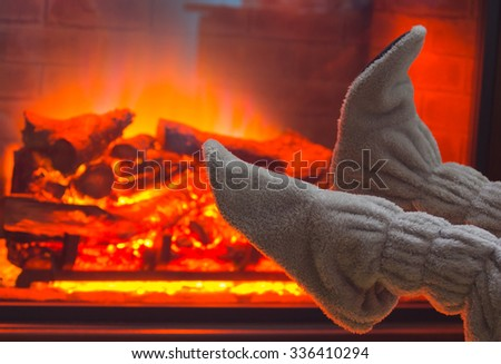 Feet in wool socks warming by cozy fireplace