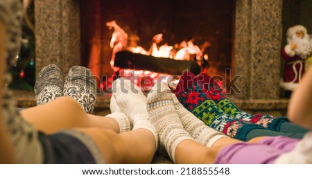 Feet in woolen socks warming by cozy fire in Christmas time. Family with two kids warming their feet by the fireplace in winter time.  - stock photo