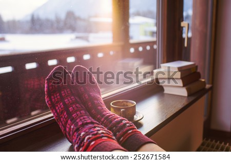 Feet in woollen socks by the Alps mountains view. Woman relaxes by mountain view with a cup of hot drink. Close up on feet. Winter and Christmas holidays concept. - stock photo