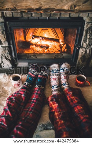 Feet in woollen socks by the Christmas fireplace. Family sitting relaxes by cozy authentic fireside with a cup of hot drink and warming up their feet. Winter and Christmas holidays concept - stock photo