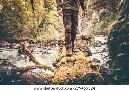 Feet Man hiking outdoor with river and forest on background Lifestyle Travel survival concept  - stock photo