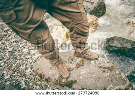 Feet Man trekking boots hiking outdoor Lifestyle Travel survival concept with river and stones on background top view