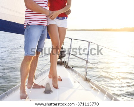 Feet of a couple on sailboat deck in the sea. Sunset - stock photo