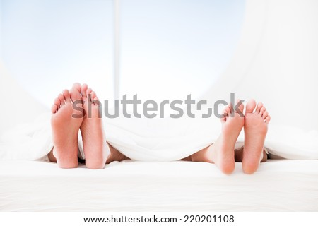 Feet of a couple sleeping side by side. - stock photo