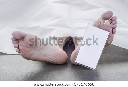 feet of a deceased man under white blanket with a blank toe tag  - stock photo