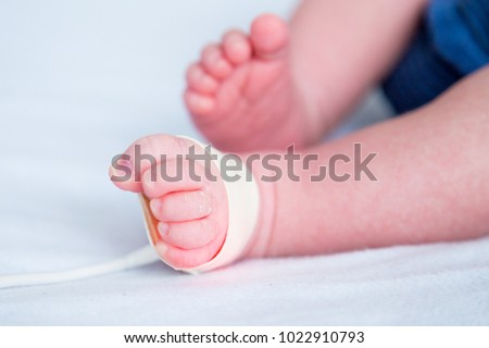 Feet of a newborn baby in hospital with oximeter to measure oxygen saturation