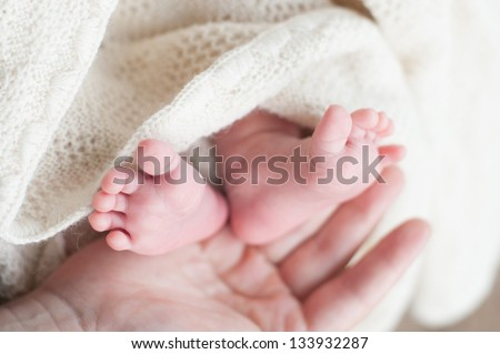 feet of a newborn girl in her mother's arms
