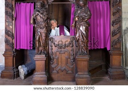 Feet of a person in a confession booth and the priest listening (shot in a medieval 17th century church) - stock photo