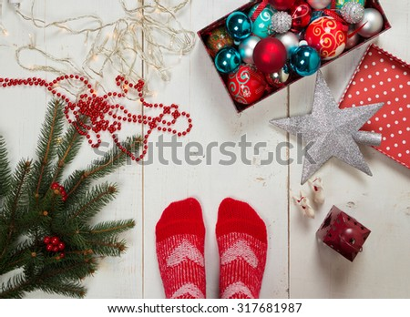 Feet of a person with red socks ready for decorating the Christmas tree surrounded by various ornaments on the floor