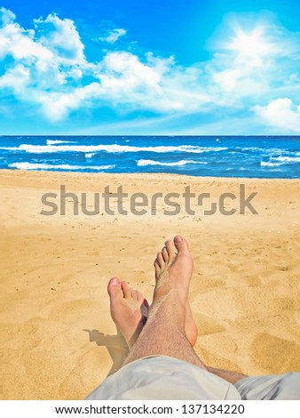 Feet of a relaxing person on a sandy beach at the ocean - stock photo