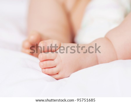 feet of a six months old baby wearing diapers lying in bed at home - stock photo