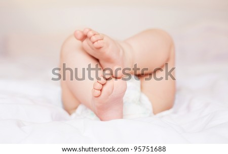 feet of a six months old baby wearing diapers lying in bed at home