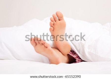 feet of a woman sleeping on the white linen at home - stock photo