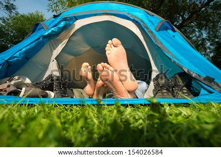 Feet of a young couple lying in a tent - stock photo