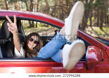 Feet of a young girl from the window of a car. Little holiday trip - stock photo