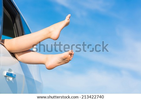 feet of a young girl from the window of a car on a background of blue sky - stock photo