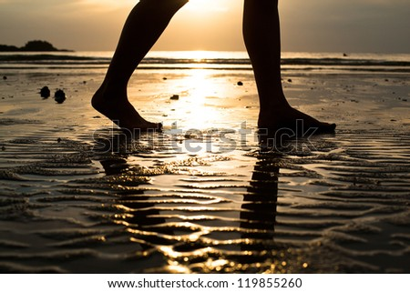 Feet of a young woman walking on the beach at sunset (backlit) - stock photo