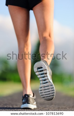 feet of an athlete running on a park pathway training for fitness and healthy lifestyle - stock photo