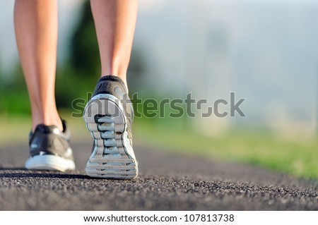 feet of an athlete running on a park pathway training for fitness and healthy lifestyle