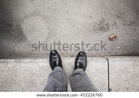 Feet of an urbanite man in black new shining shoes standing on gray curb