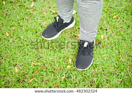 Feet of asian woman wearing sport running shoes on grass field. Fitness and Health background concept.