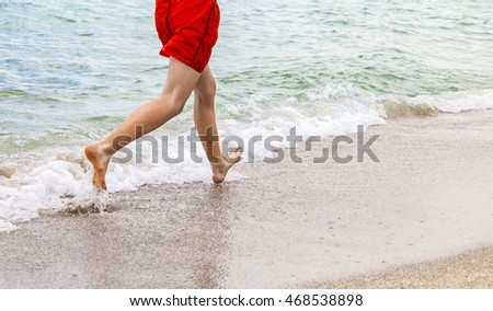feet of boy running along the beach in the water
