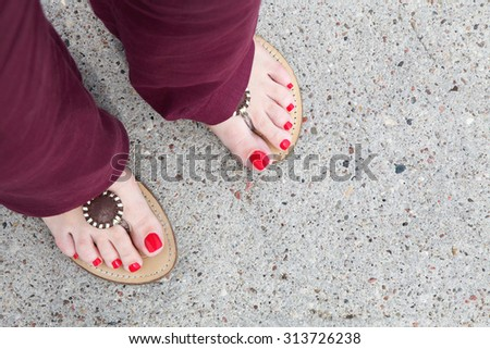 feet of caucasian woman red nails pedicure and flip-flops - stock photo
