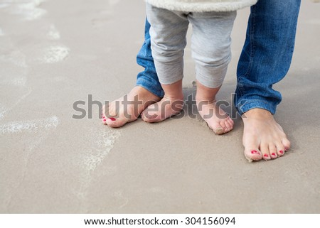 Feet of child and mom on the sand - stock photo