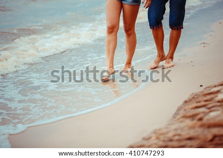 feet of couple. Woman and man in the sea waves on sunset