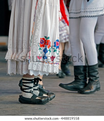 Feet of dancers and clothes in traditional Romania folk dances. - stock photo