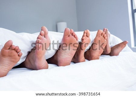 Feet of family sticking out from white quilt in bedroom - stock photo
