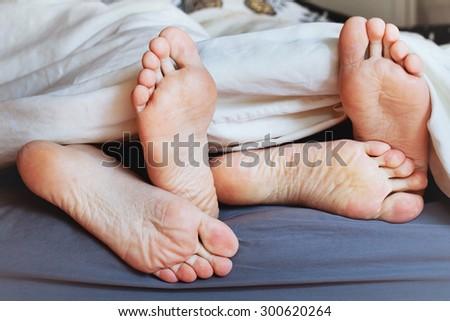 feet of family under blanket, happy morning of loving couple - stock photo