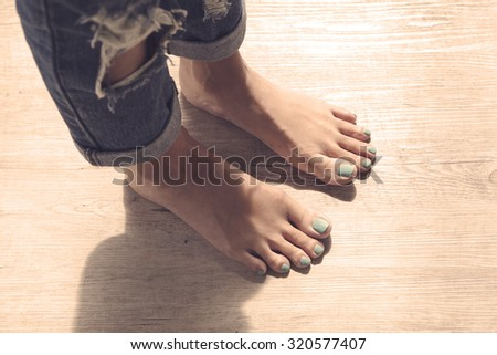 Feet of girl on wooden floor.