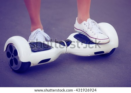 Feet of girl riding electric mini hover board scooter outdoors in park. Ecological city transportation on battery power, produces no air pollution to atmosphere - stock photo