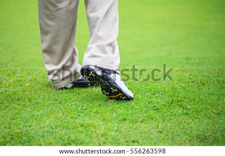 Feet of golfers on a golf course after hitting the golf ball.