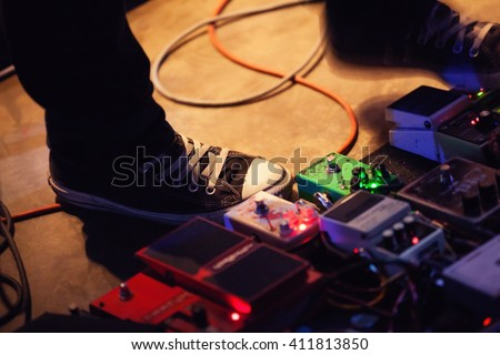 Feet of guitar player on a stage with set of distortion effect pedals. Selective focus - stock photo